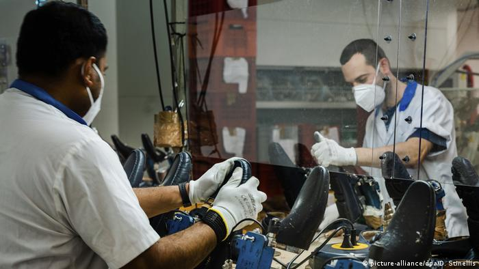 Shoe manufacturers in Italy work wearing face masks and seperated from each other with clear plastic screens.