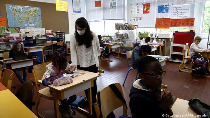 A classroom at a school in Europe, with a teacher and pupils wearing face masks