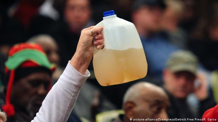 In this image from 2015 a resident of Flint holds up a sample of water that came her home after the authorities changed the source of the town's drinking water