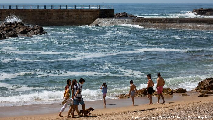 People take a stroll along a beach and play in the waves in Porto, Portugal on the first day of the lockdown being lifted.