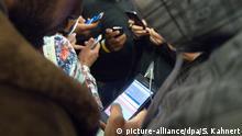 ARCHIV - Flüchtlinge schauen am 06.09.2015 in einer Flüchtlingsunterkunft in Hermsdorf (Thüringen) auf ihre Smartphones, um mit Angehörigen und Freunden zu kommunizieren. Die norwegische Regierung will künftig Handys und Computer von Asylbewerbern routinemäßig kontrollieren, um Terror vorzubeugen. (zu dpa Norwegen will Handys von Asylbewerbern routinemäßig kontrollieren vom 03.03.2017) Foto: Sebastian Kahnert/dpa-Zentralbild/dpa +++(c) dpa - Bildfunk+++ | Verwendung weltweit
