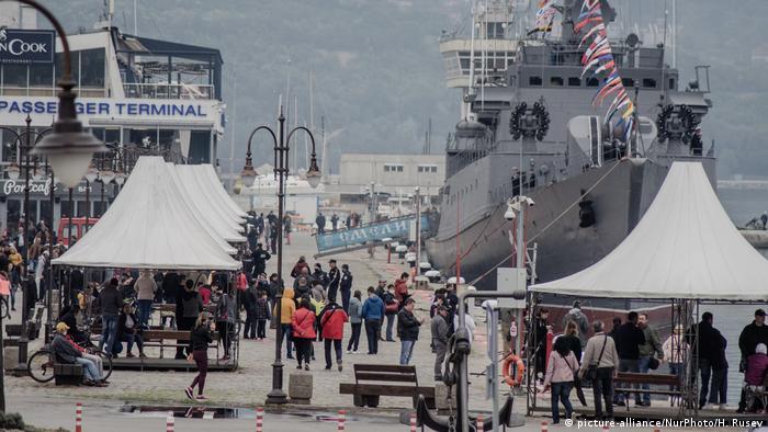 People walk past a Navy ship docked in Varna