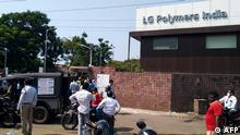 Policemen stand guard as people gather in front of an LG Polymers plant following a gas leak incident in Visakhapatnam on May 7, 2020. - At least five people have been killed and several hundred hospitalised after a gas leak at a chemicals plant on the east coast of India, police said on May 7. They said that the gas had leaked out of two 5,000-tonne tanks that had been unattended due to India's coronavirus lockdown in place since late March. (Photo by - / AFP)