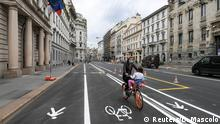 A woman and a child ride a bicycle as Milan reallocates road space previously used by cars to new bicycle lanes and pedestrian pathways, as part of an effort to reduce pollution ahead of lockdown gradually lifting due to a spread of the coronavirus disease (COVID-19), in Milan, Italy April 30, 2020. REUTERS/Daniele Mascolo