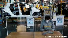 An employee, wearing a protective face mask, sits at a table with plastic barriers to maintain social distancing as he works on the automobile assembly line of Renault ZOE cars at the Renault automobile factory in Flins as the French carmaker ramps up car production with new security and health measures during the outbreak of the coronavirus disease (COVID-19) in France, May 6, 2020. (Reuters/G. Fuentes)