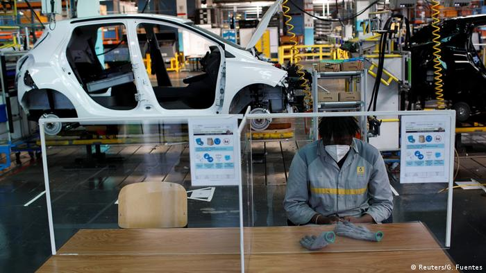 An employee, wearing a protective face mask, sits at a table with plastic barriers to maintain social distancing as he works on the automobile assembly line of Renault ZOE cars at the Renault automobile factory in Flins as the French carmaker ramps up car production with new security and health measures during the outbreak of the coronavirus disease (COVID-19) in France, May 6, 2020.