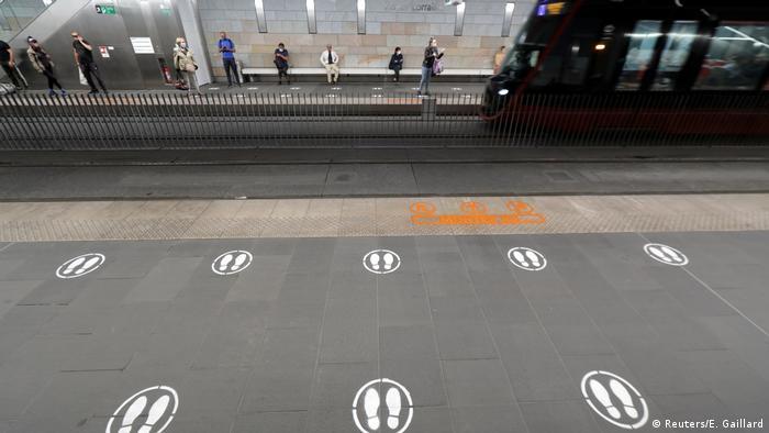 Соціальне дистанціювання на пероні У найближчі місяці дотримуватися необхідної відстані людям доведеться не лише в приміщеннях. На станції метро у французькій Ніцці відбитки взуття вказують на те, де можна чекати на прибуття поїзда. Подібні приклади є в усьому світі. Однак це навряд чи допоможе уникнути скупчення людей під час посадки.