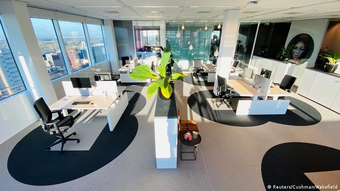 Офис, в котором черными кругами вокруг рабочих мест обозначено расстояние, на которое можно приближаться к коллегам