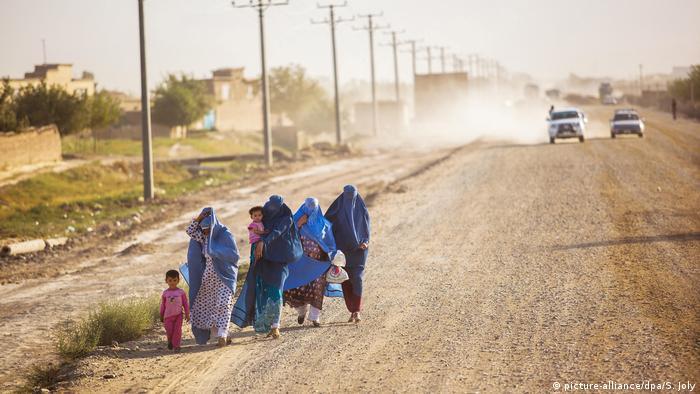 Perempuan dan anak-anak Afghanistan di tepi sebuah jalan penghubung utama menuju Parwan.
