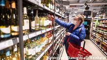 24.04.2020, Hamburg: Eine Frau greift in einem Supermarkt nach einer Flasche Wein. In der Corona-Krise wird in den Hamburger Supermärkten zeitweise deutlich mehr Alkohol eingekauft. Foto: Daniel Reinhardt/dpa +++ dpa-Bildfunk +++ | Verwendung weltweit
