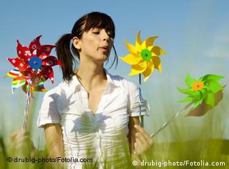 Junge Frau mit farbigen Windrädern in der Hand (Quelle: Fotolia)