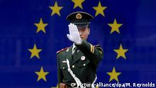 A Chinese police officer in front of an EU flag
