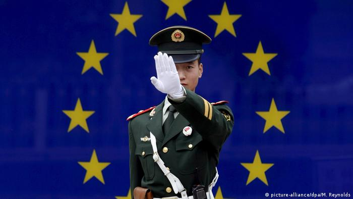 A Chinese police officer holds out his hand in front of an EU flag (picture-alliance/dpa/M. Reynolds)