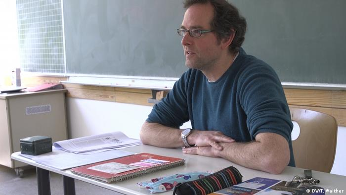 Lehrer Florian Quaiser sitzt am Pult vor der Tafel