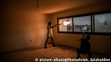 (200419) -- TRIPOLI, April 19, 2020 () -- A fighter of the UN-backed Government of National Accord (GNA) fires his weapon during clashes with Libyan National Army (LNA) at Salah Al-Din frontline in Tripoli, Libya, April 18, 2020. Libya's UN-backed government's forces said they launched 17 airstrikes on the east-based army positions in Tarhuna, some 90 kilometers south of the capital Tripoli, seizing a number of military vehicles. Despite international call for cease-fire in Libya, the deadly armed conflict has continued with collateral civilian casualties. (Photo by Amru Salahuddien/)  