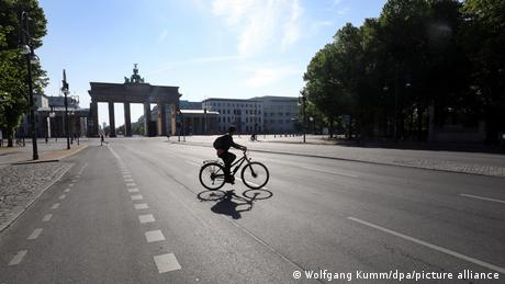 A person riding a bike in front of the Brandenburg Gate