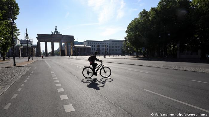 A lone bike-rider in front of the Brandeburg Gate in Berlin