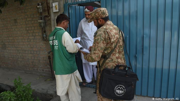 A soldier collects information from an Ahmadi sect resident