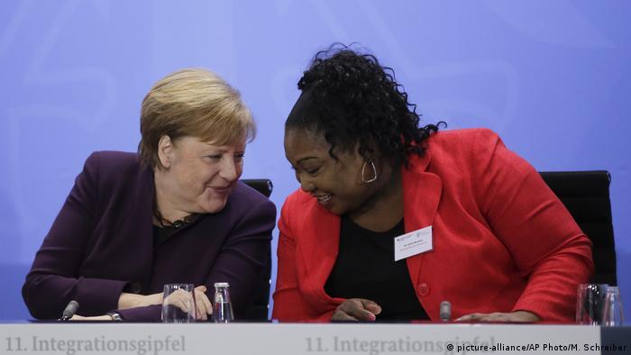 Angela Merkel speaks with Sylvie Nantcha at the integration summit in Berlin, Germany