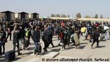 18.3.2020, Afghanistan, thousands of Afghan refugees walk as they enter Afghanistan at the Islam Qala border crossing with Iran, in the western Herat Province. Some 200,000 Afghans and counting have returned from Iran to their home country after losing their jobs in the coronavirus pandemic or out of fear of getting infected. They are flowing across the border from a country that has one of the world's worst outbreak to an impoverished nation that is woefully unprepared to deal with the virus. (AP Photo/Hamed Sarfarazi, File) |