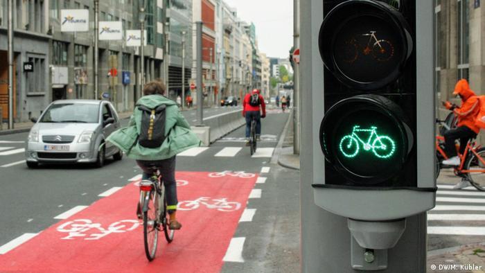 Cyclists ride down a bike lane beside a green traffic light