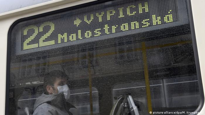 A man wearing a mask on a tram in Prague