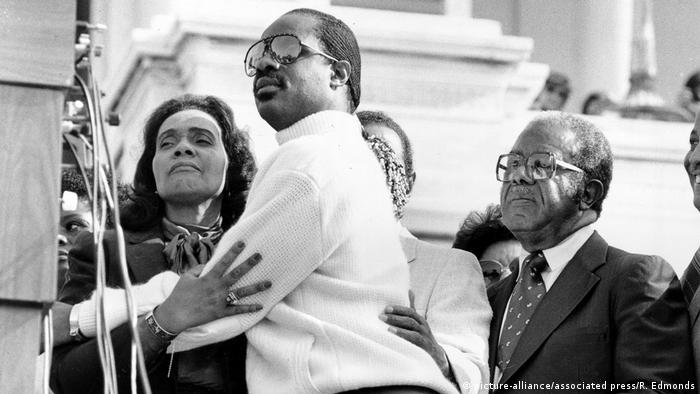 oretta Scott King, widow of the Rev. Martin Luther King Jr., embraces singer Stevie Wonder during a celebration on the steps of the U.S. Capitol Building in Washington, D.C., Nov. 3, 1983, after U.S. President Ronald Reagan signed a bill making the civil rights leader's birthday (picture-alliance/associated press/R. Edmonds)
