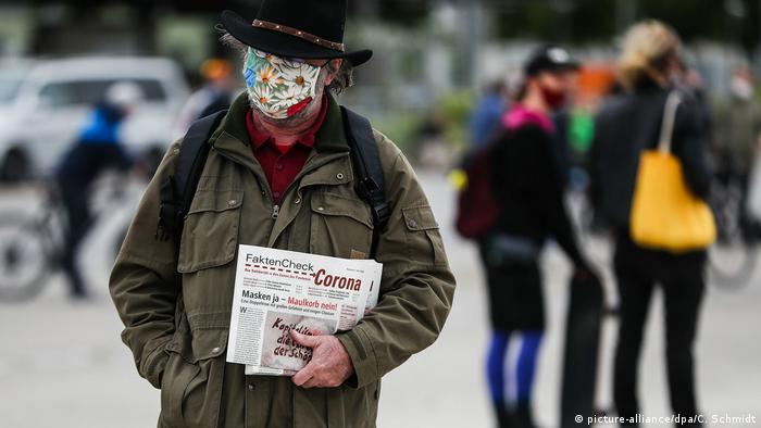 A protester in Stuttgart wears a mask