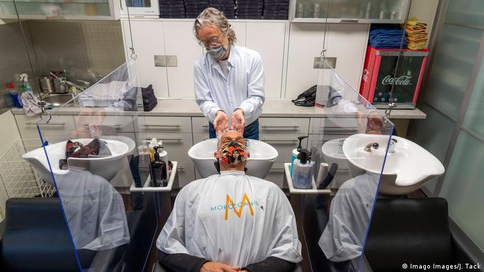 Парикмахер в маске моет голову клиенту