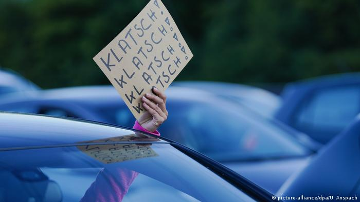 Водитель машины держит в руках кусок картона, на котором написано аплодирую