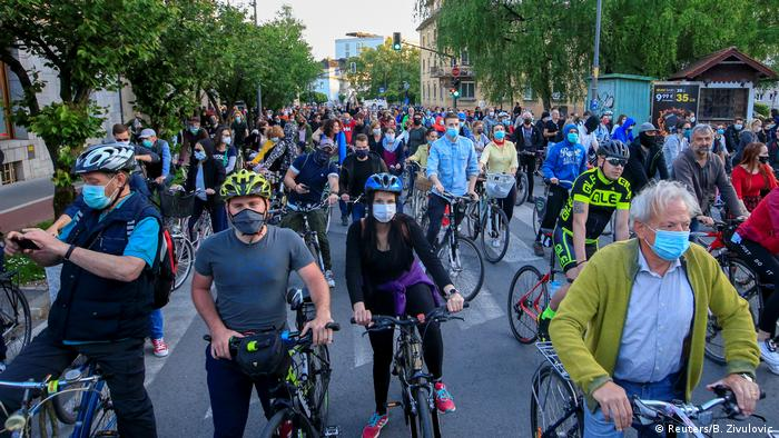 Protesters wearing protective face masks ride bicycles during an anti-government protest