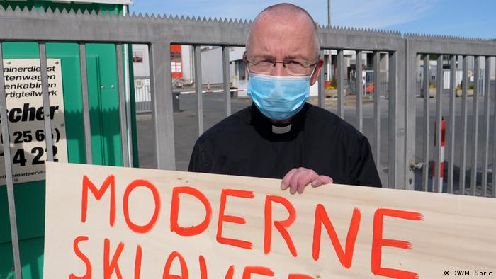 Patrick Peter Kossen holds up a sign reading 'end modern slavery'