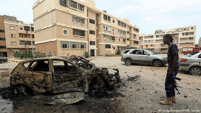 A man with a gun stands next to a burnt-out car in Tripoli