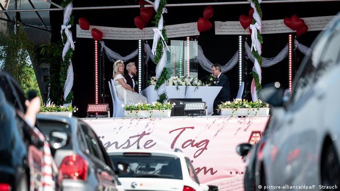 Сказати так перед 30 машинами Хто сказав, що весілля в часи пандемії повинні проходити без гостей? Ця молода пара наречених вирішила провести весільну церемонію в автомобільному кінотеатрі в Дюссельдорфі, гості стежили за дійством через свої радіоприймачі та голосно засигналили після вирішального так. Це було перше в Німеччині весілля в автокінотеатрі, але не останнє.
