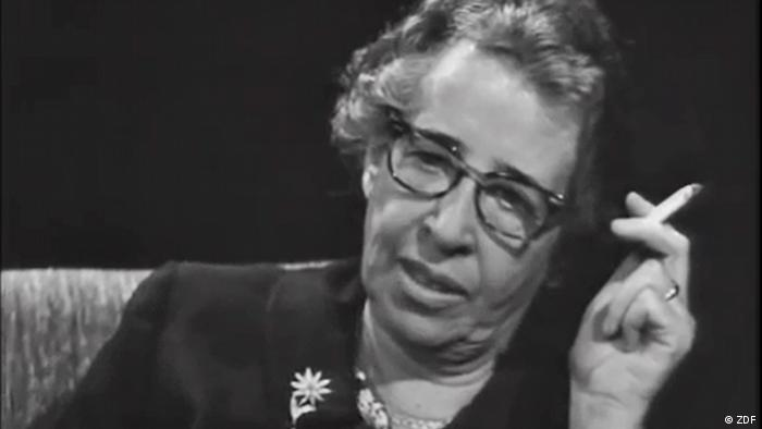 Foto em preto e branco de mulher sentada, de óculos com cigarro na mão