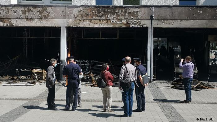 Policjanci i śledczy przed wypalonym tureckim sklepem w Waldkraibug
