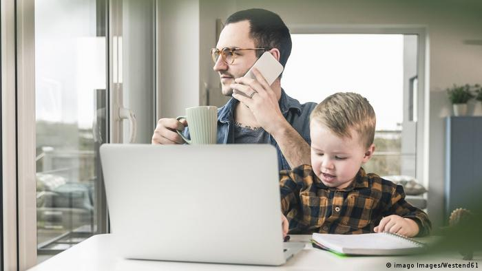 Father working at table in home office with son sitting on his lap model released Symbolfoto property released