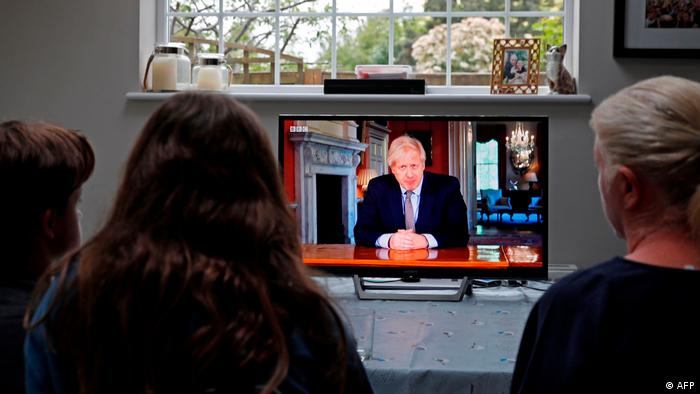 A family gather around the television to watch Britain's Prime Minister Boris Johnson give a televised message to the nation