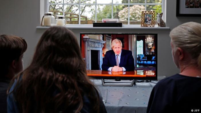 بريطانيون يتابعون خطاب جونسون عبر شاشة التلفاز