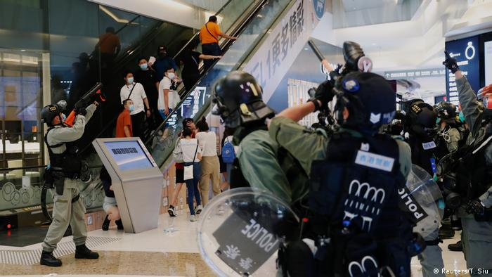 Police point their weapons in a Hong Kong mall