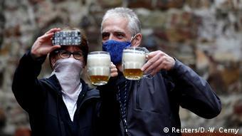Мужчина и женщина в масках делают селфи с пивом в руках в центре Праги