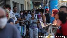SAO GONCALO, BRAZIL - MAY 05: People using protective masks wait in line outside a Caixa Economica Federal bank branch in Ze Garoto neighborhood to receive urgent government benefit amidst the coronavirus (COVID - 19) pandemic May 05, 2020 in Sao Goncalo, Brazil.Brazil's government has launched a financial aid plan for the humble families of Brazil affected by the coronavirus crisis. (Photo by Luis Alvarenga/Getty Images)