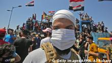 TOPSHOT - An Iraqi protester wears a face mask during an anti-government demonstration on Al-Jumhuriyah bridge in the capital Baghdad, on May 10,2020. - Modest anti-government rallies resumed in some Iraqi cities today, clashing with security forces and ending months of relative calm just days after Prime Minister Mustafa Kadhemi's government came to power. (Photo by AHMAD AL-RUBAYE / AFP) (Photo by AHMAD AL-RUBAYE/AFP via Getty Images)