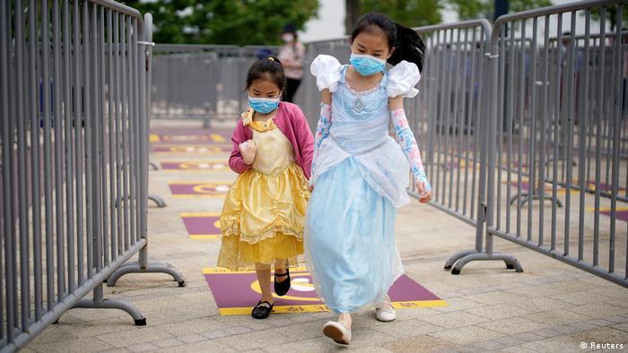 Duas garotas com máscaras e vestidos de princesa aproveitam a reabertura da Disneylândia em Xangai