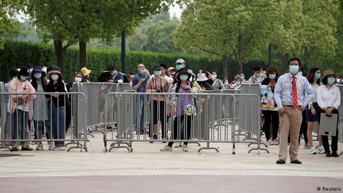 Foto de personas haciendo fila con mascarillas