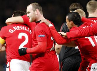Manchester United's Wayne Rooney, second left, is congratulated by teammates after scoring a goal against AC Milan's during their Champions League first knockout round second leg soccer match at Old Trafford Stadium, Manchester, England, Wednesday March 10, 2010. (AP Photo/Antonio Calanni)