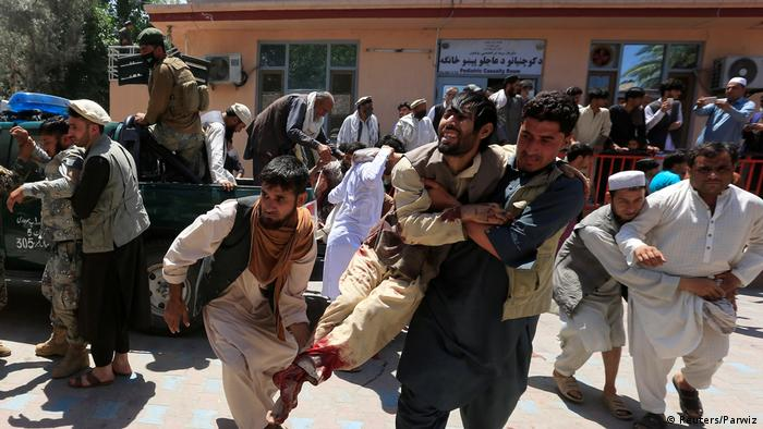 Men carry an injured person to a hospital after a blast during a funeral ceremony in Jalalabad, Afghanistan