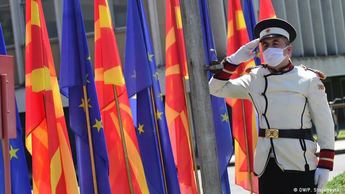 A person salutes flags from North Macedonia and the EU (DW/P. Stojanovski )