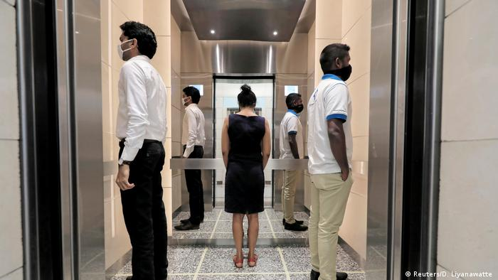 People practice social distancing inside an elevator prior to arriving to their work places at World Trade Center, after the government announced that private and state companies will reopen their offices