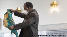 04.05.2020, Hessen, Frankfurt/Main: Mit seinem Gebetsteppich kommt ein Mann zum Gebet in die Abu-Bakr-Moschee in Frankfurt. Zum Mittagsgebet durfte die Moschee erstmals seit acht Wochen wieder öffnen. Aus Hygiene-Gründen hat der Moschee-Vorstand verfügt, dass die Betenden neben dem obligatorischen Mundschutz auch ihren eigenen Gebetsteppich mitbringen müssen. Foto: Boris Roessler/dpa | Verwendung weltweit